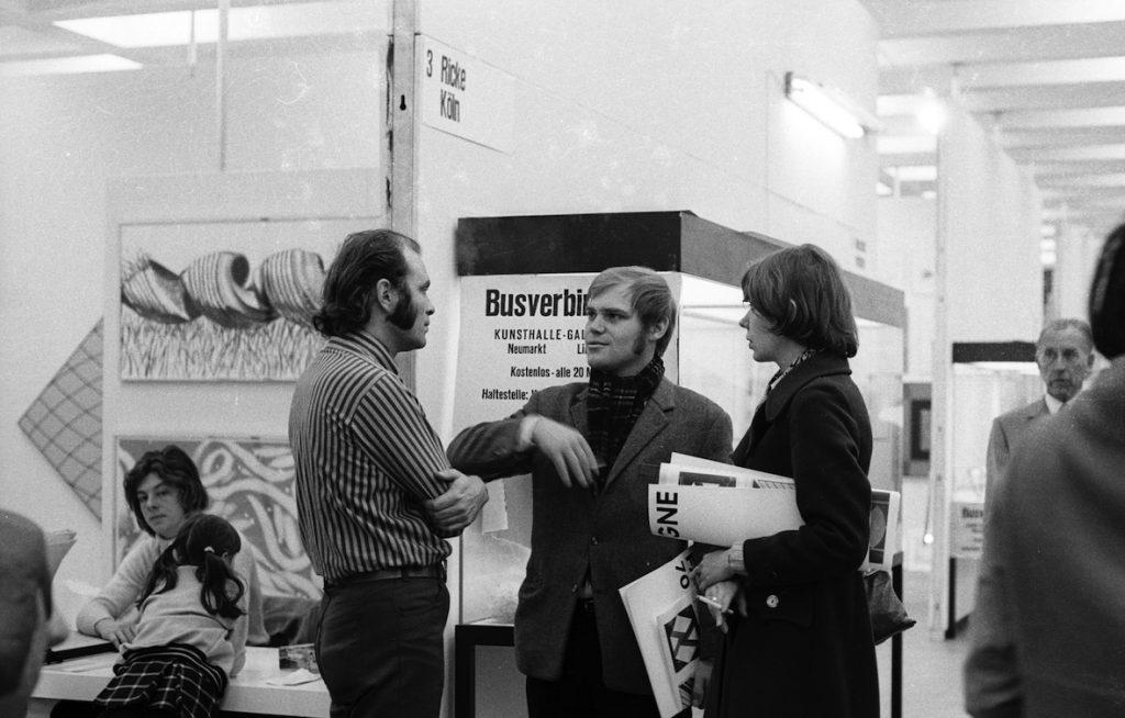 Rolf Ricke im Gespräch vor seiner Koje, Kunstmarkt Köln, 1970. Foto: © Johanna Schmitz-Fabri, ZADIK